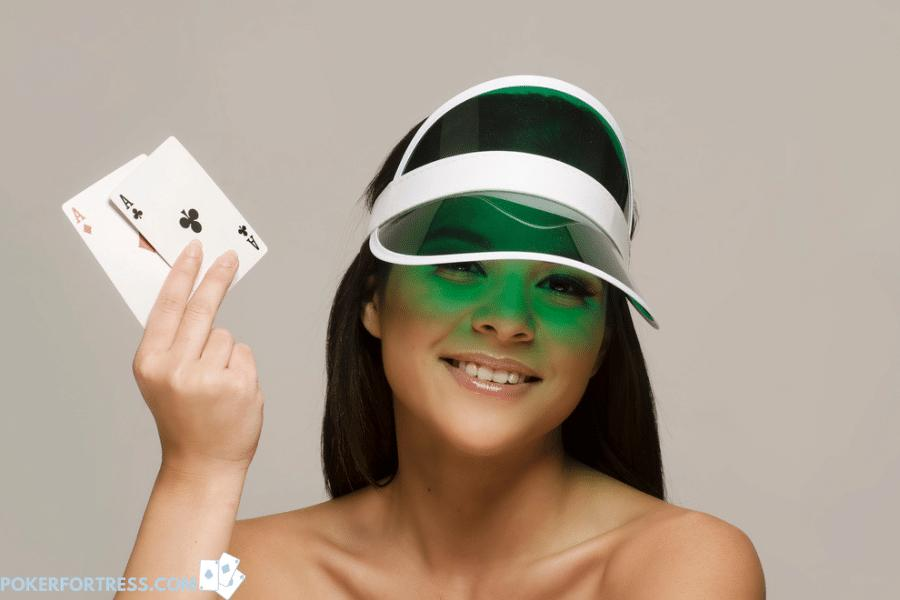Poker dealer wearing a green visor because of light.